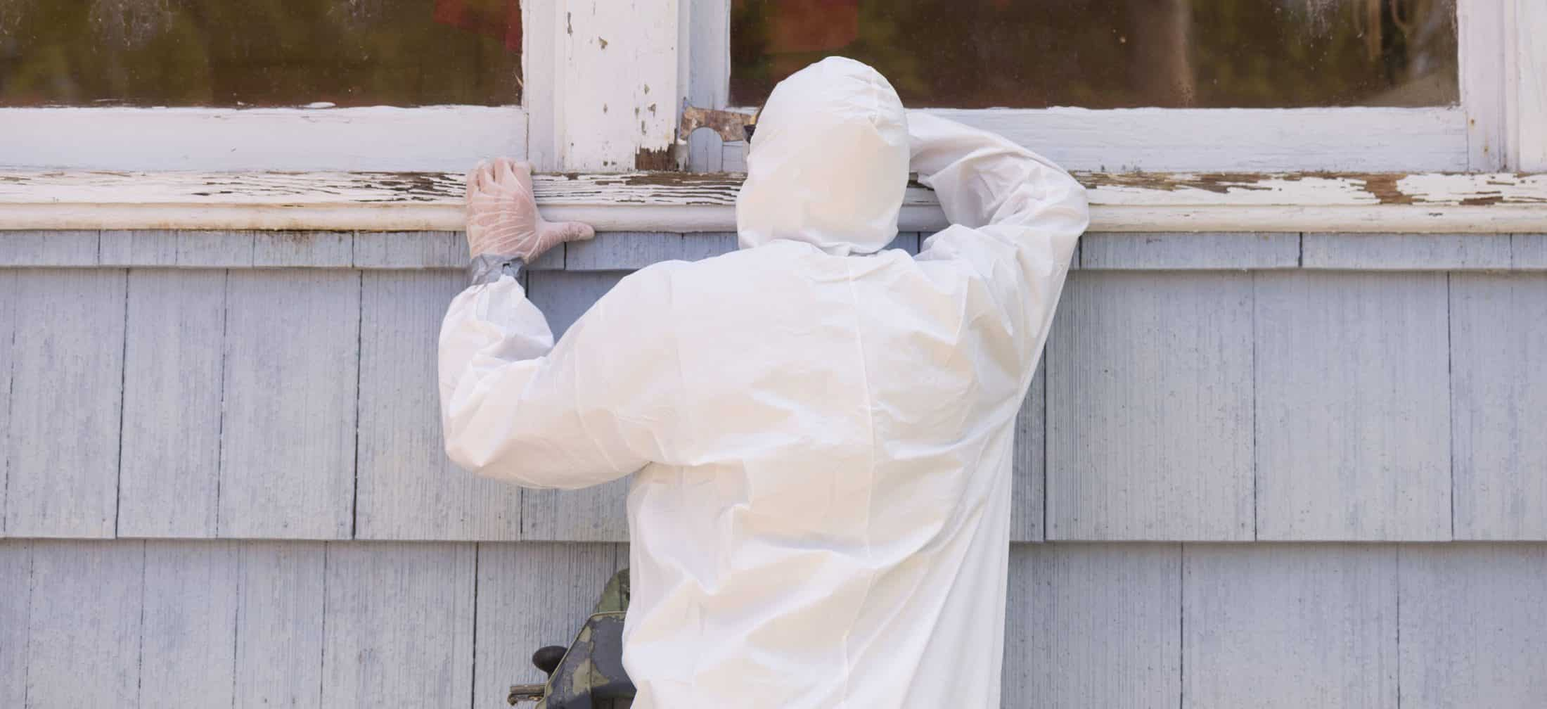 Hazardous materials removal specialist removing lead paint from a window sill