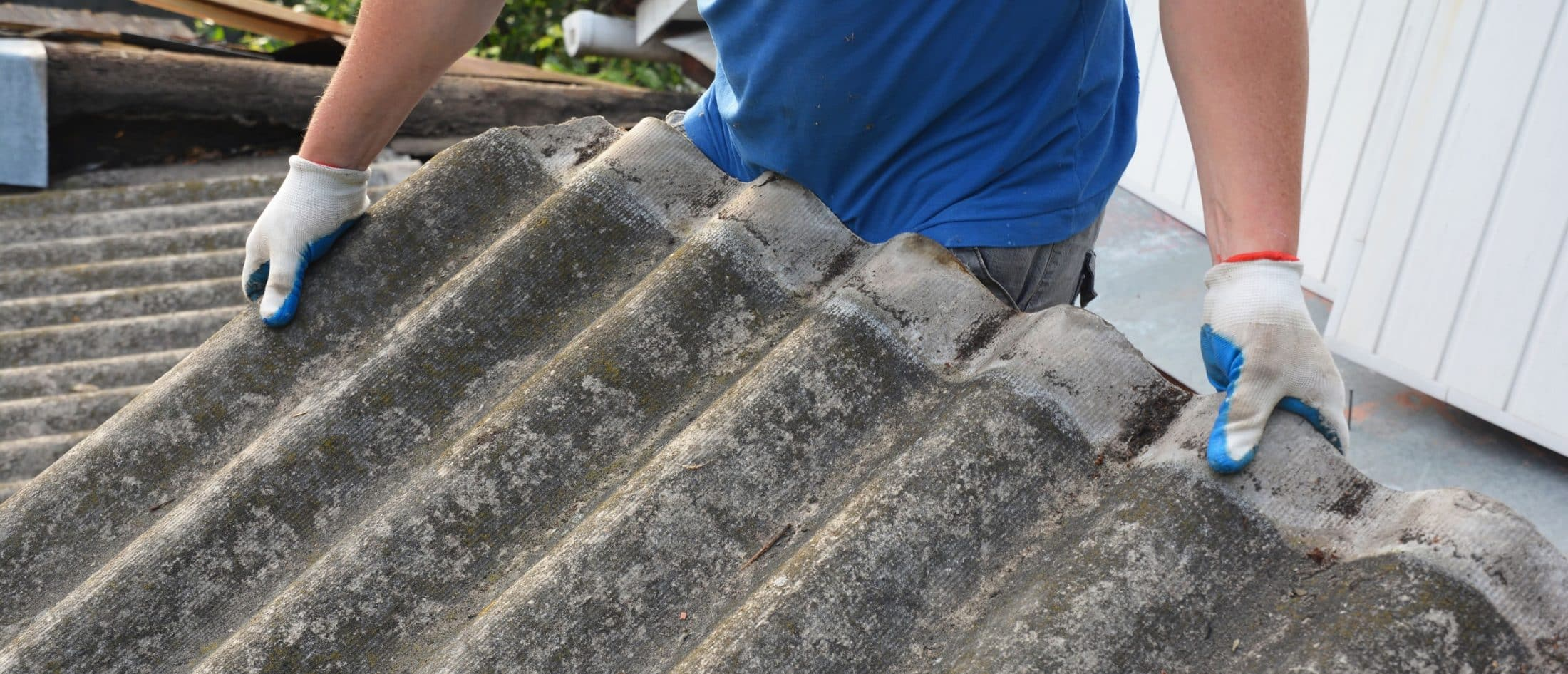 Worker removing asbestos shingles
