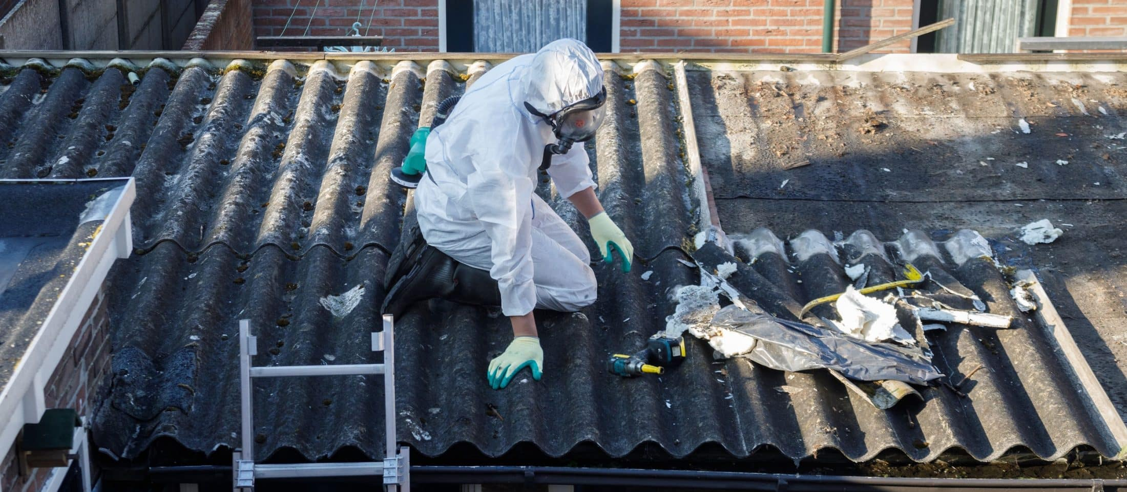 Worker in protective gear removing asbestos shingles