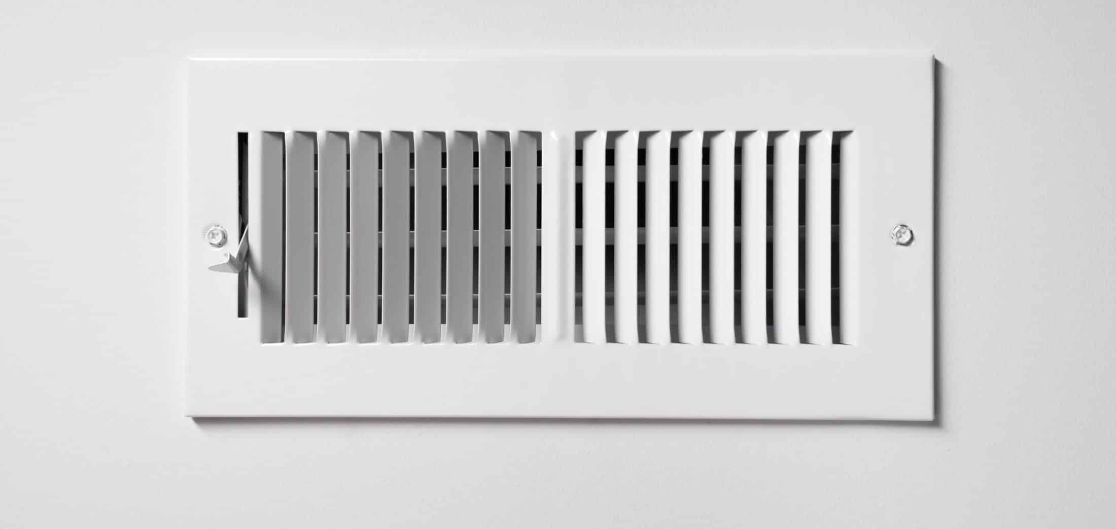 A heating and cooling vent register on the wall of a home