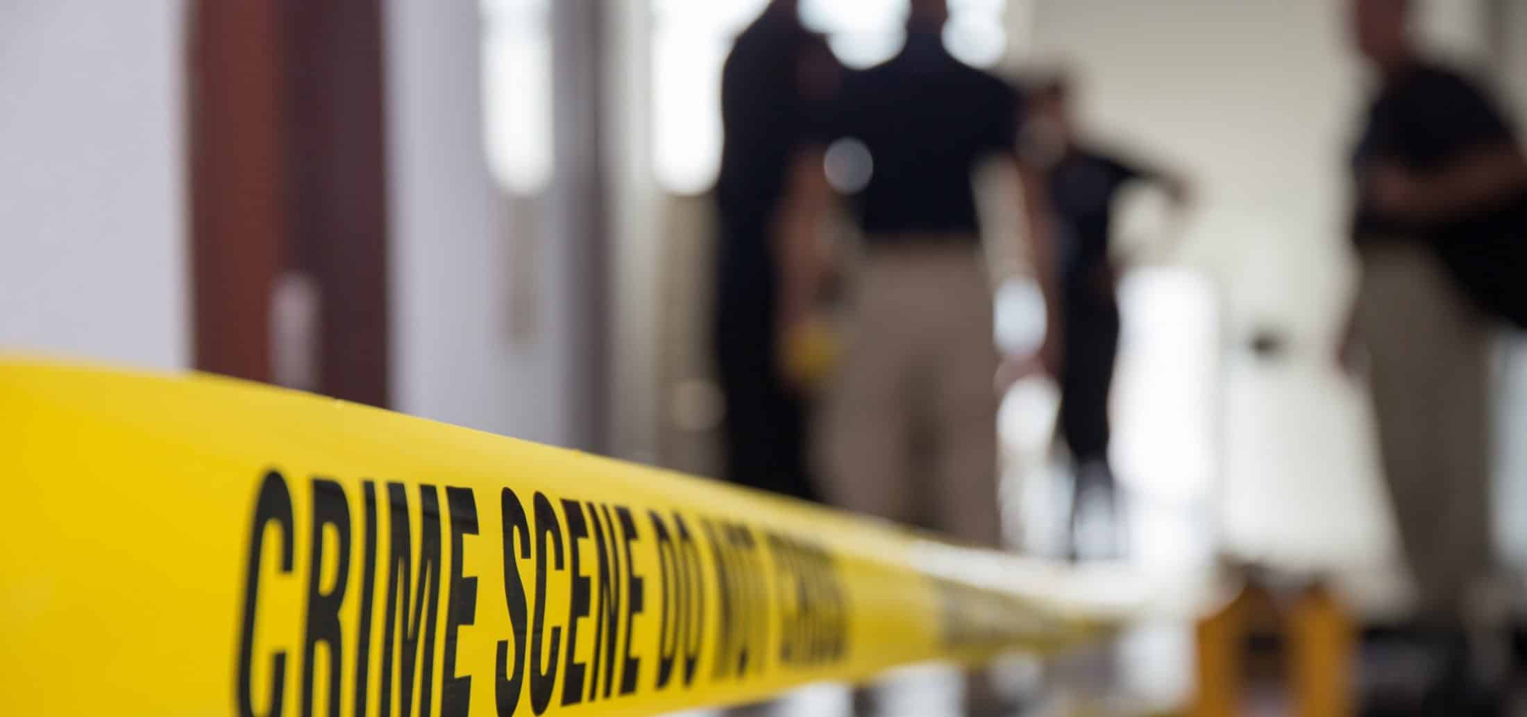 Crime scene tape and forensic team inside of a home